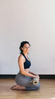 Femme sportive avec un tapis de yoga