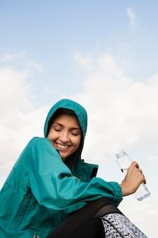 Femme sportive tenant une bouteille d'eau