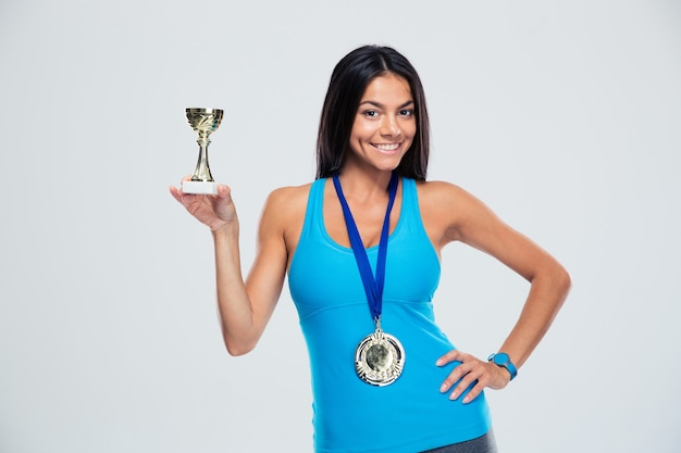 Femme sportive tenant la coupe du vainqueur