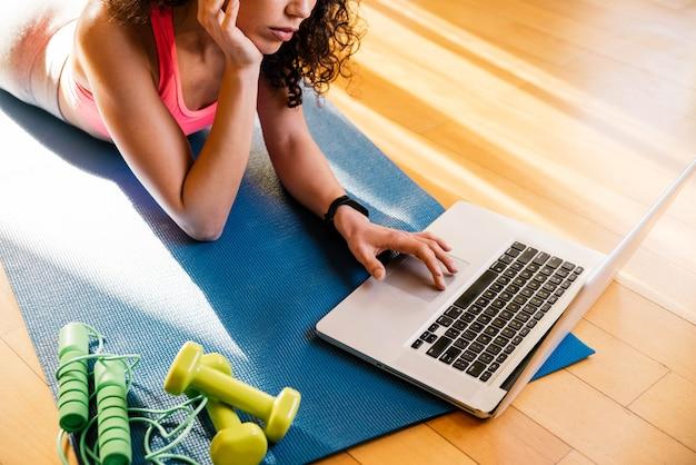 Femme sportive en tenue de sport est assise sur le sol avec des haltères à l'aide d'un ordinateur portable dans le salon