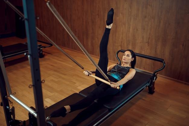 Femme sportive en tenue de sport faisant des exercices d'étirement de pilates dans la salle de gym. workuot de remise en forme dans un club de sport.