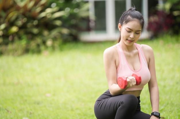 Une femme sportive en tenue de sport s'exerce dans le jardin devant sa maison