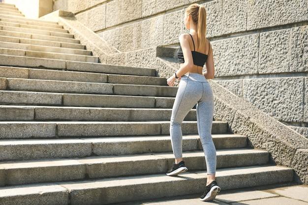 Femme sportive travaillant à courir vers le haut des escaliers à l'extérieur pour l'entraînement du matin