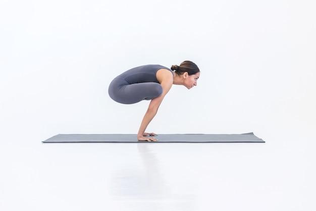 Une femme sportive yogi pratique le yoga debout sur les mains en pose de coq