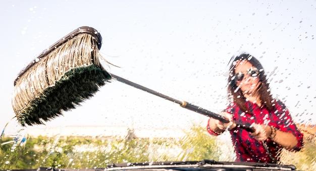 Femme à la station de lavage de voiture