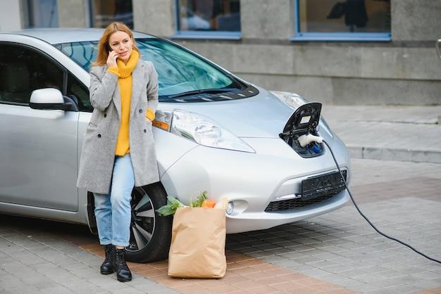 Femme sur la station de recharge de voitures électriques pendant la journée