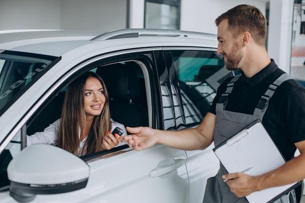 Femme à la station-service acr vérifiant sa voiture avec mécanicien