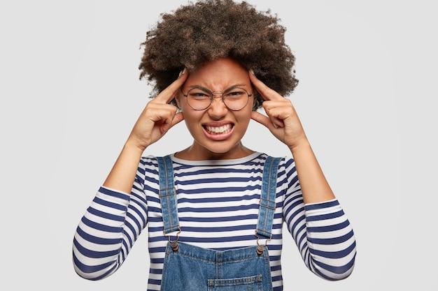 Une femme stressante à la peau sombre souffre de maux de tête terribles, garde les doigts de l'avant sur les tempes, serre les dents avec douleur, vêtue d'un pull rayé et d'une salopette en denim, pose contre un mur blanc