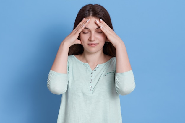Femme stressée agacée en gardant les doigts sur le front