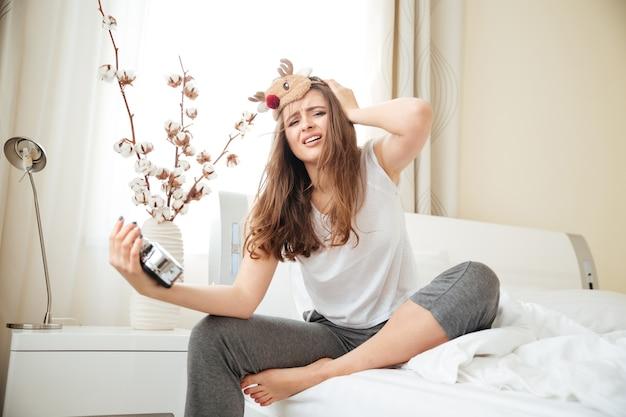 Femme stressée assise sur le lit avec réveil à la maison
