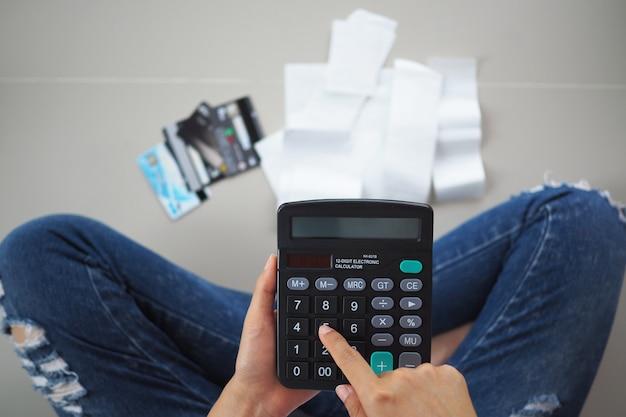 Femme stressée calculant les dépenses de recettes
