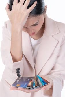 Femme stressée détenant de nombreuses cartes de crédit avec une énorme dette, concept d'argent pour créances irrécouvrables