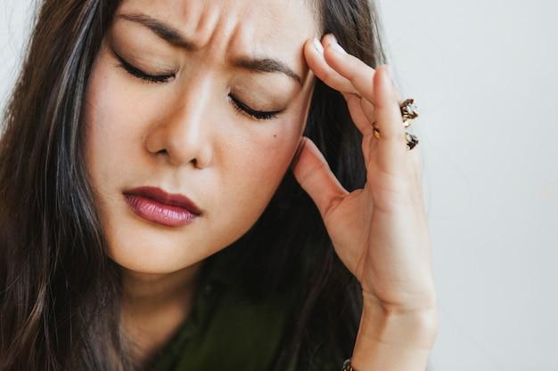 Femme stressée tenant son front