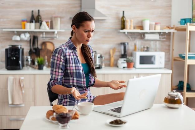 Femme stressée utilisant un ordinateur portable dans la cuisine pendant le petit-déjeuner avec une tasse de thé vert
