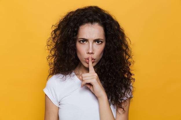 Femme stricte des années 20 aux cheveux bouclés tenant le doigt sur les lèvres isolées sur jaune