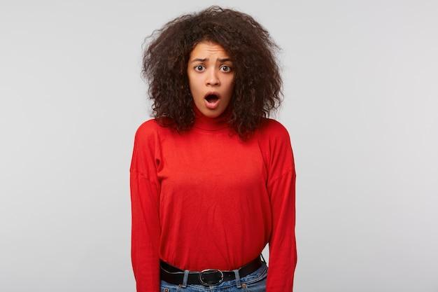 Une femme stupéfaite avec une coiffure afro regarde devant et garde la bouche ouverte, regarde étonnamment