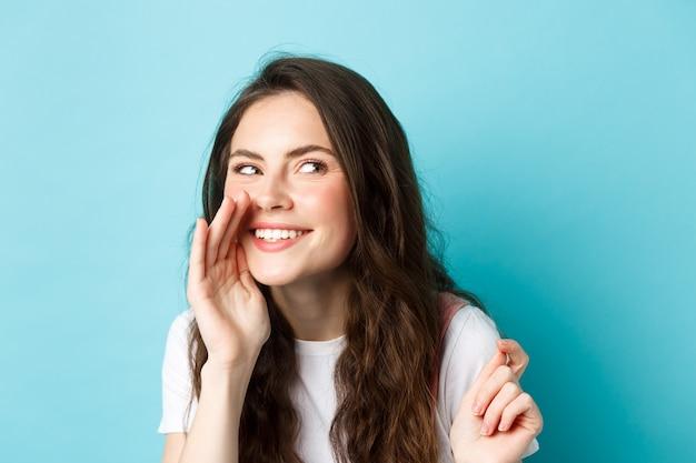 Une femme stupide et rusée répandait des commérages, parlant à voix basse, racontant des rumeurs, souriant et riant à droite, debout sur fond bleu.