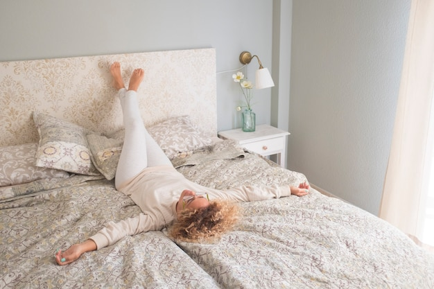 Femme De Style De Vie à La Maison Se Relaxant Le Matin Sur Le Lit Dans La Chambre à Coucher Photo Premium