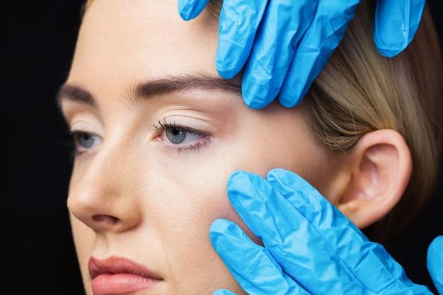 La femme subit un examen de sa peau avant l'injection