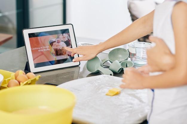 Femme suivant un didacticiel vidéo en essayant une nouvelle recette de gâteau à la maison