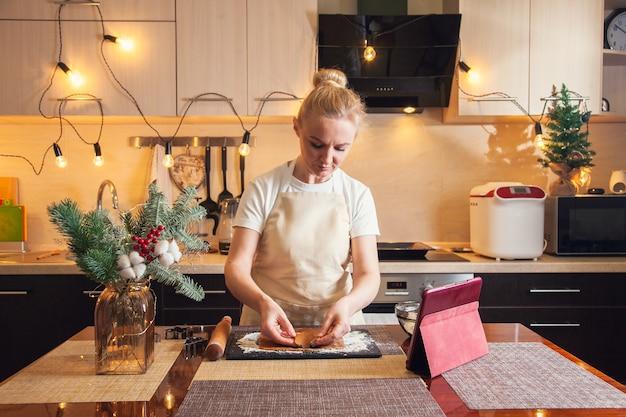 Femme suivant la recette sur tablette numérique et préparant des biscuits au pain d'épice de noël dans sa cuisine.