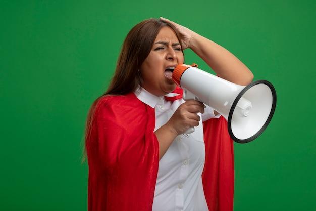 Femme de super-héros d'âge moyen en colère à la recherche de côté parle sur haut-parleur isolé sur fond vert
