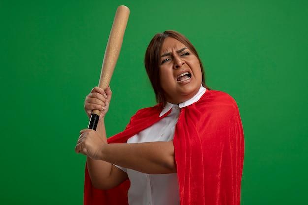 Femme de super-héros d'âge moyen en colère regardant le côté soulevant la batte de baseball isolé sur vert
