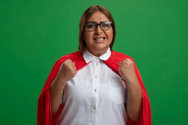 Femme de super-héros d'âge moyen concerné portant des lunettes montrant oui geste isolé sur vert