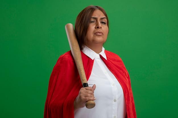 Femme de super-héros d'âge moyen confiant mettant la batte de baseball sur l'épaule isolé sur vert