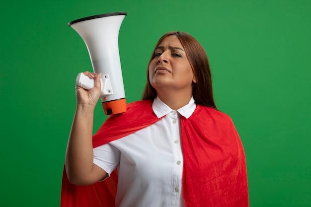 Femme de super-héros d'âge moyen confiant mettant haut-parleur sur l'épaule isolé sur vert