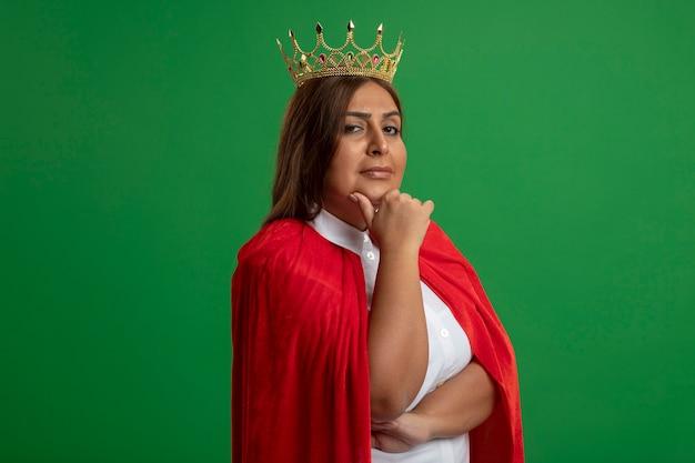 Femme de super-héros d'âge moyen confiant portant couronne mettant la main sur le menton isolé sur vert