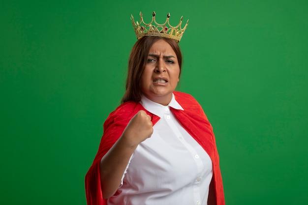 Femme de super-héros d'âge moyen confiant portant couronne montrant oui geste isolé sur fond vert