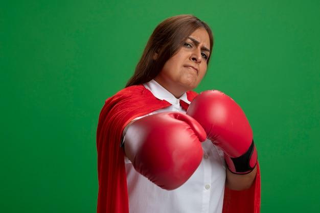 Femme de super-héros d'âge moyen confiant portant des gants de boxe tenant la main isolée sur vert