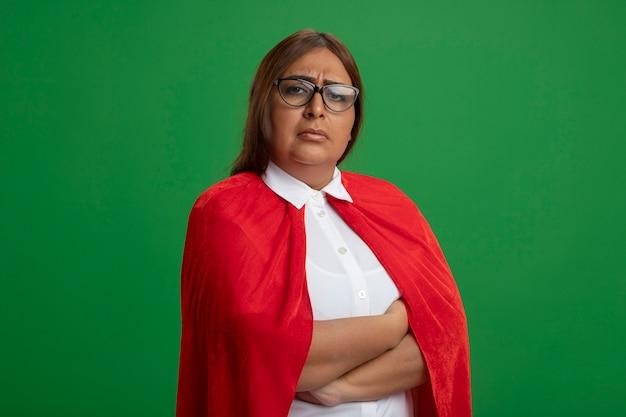 Femme de super-héros d'âge moyen confiant portant des lunettes croisant les mains isolées sur le vert