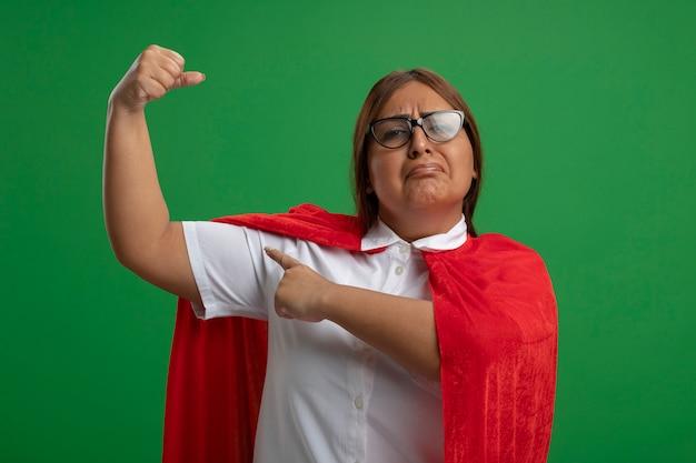 Femme de super-héros d'âge moyen confiant portant des lunettes montrant un geste fort isolé sur vert
