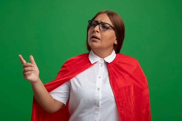 Femme de super-héros d'âge moyen confus portant des lunettes points sur le côté isolé sur fond vert