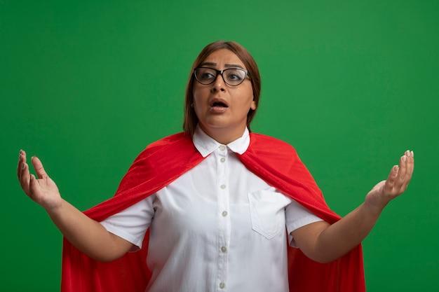 Femme de super-héros d'âge moyen confus regardant côté portant des lunettes répandant les mains isolées sur le vert