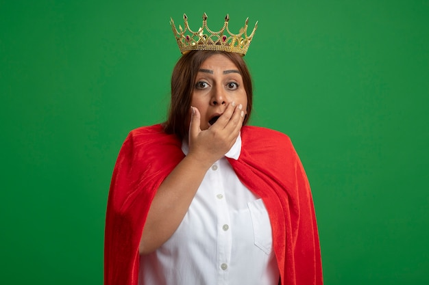 Femme de super-héros d'âge moyen effrayée portant la bouche couverte de couronne avec la main isolée sur fond vert