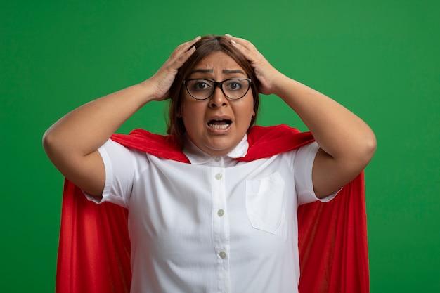 Femme de super-héros d'âge moyen effrayée portant des lunettes a saisi la tête isolée sur fond vert