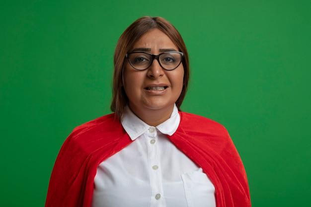 Femme de super-héros d'âge moyen insatisfaite portant des lunettes regardant la caméra isolée sur fond vert