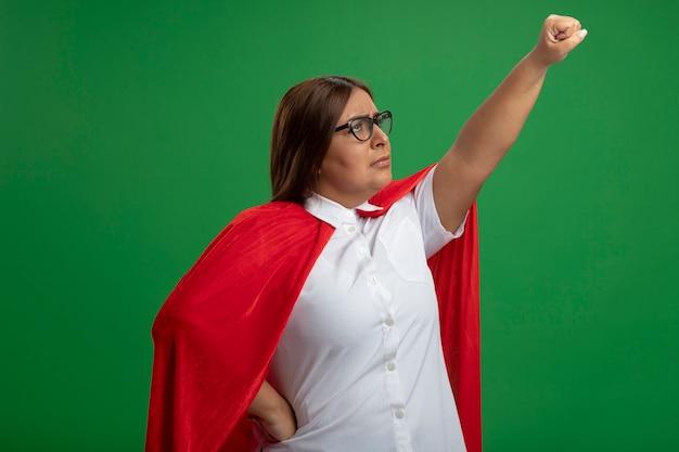 Femme de super-héros d'âge moyen malheureux levant le poing portant des lunettes isolées sur le vert