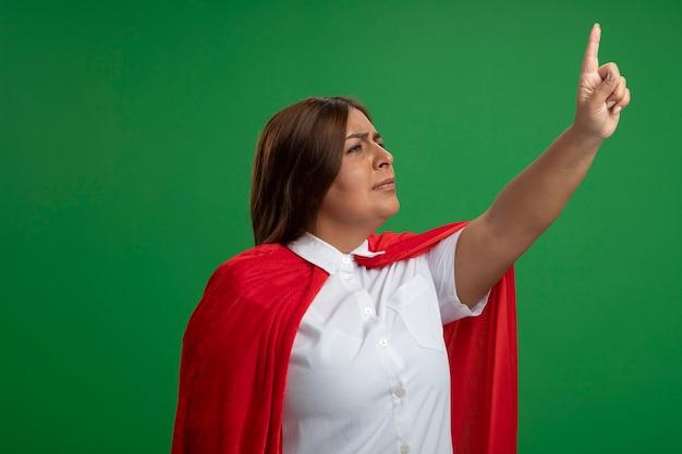 Femme de super-héros d'âge moyen à la recherche de points latéraux à up isolated on green