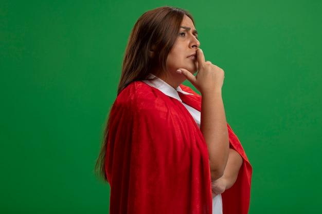 Femme de super-héros d'âge moyen réfléchie à côté de mettre la main sur le menton isolé sur vert