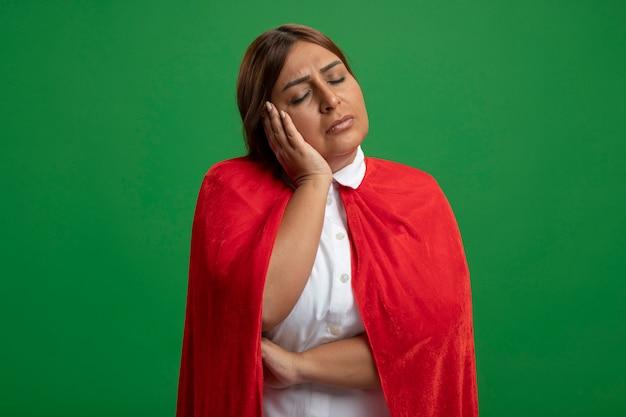 Femme de super-héros d'âge moyen avec les yeux fermés montrant le geste de sommeil isolé sur fond vert