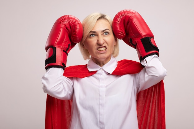 Femme super-héros blonde d'âge moyen agressive en cape rouge portant des gants de boîte touchant la tête avec les poings regardant le côté montrant les dents