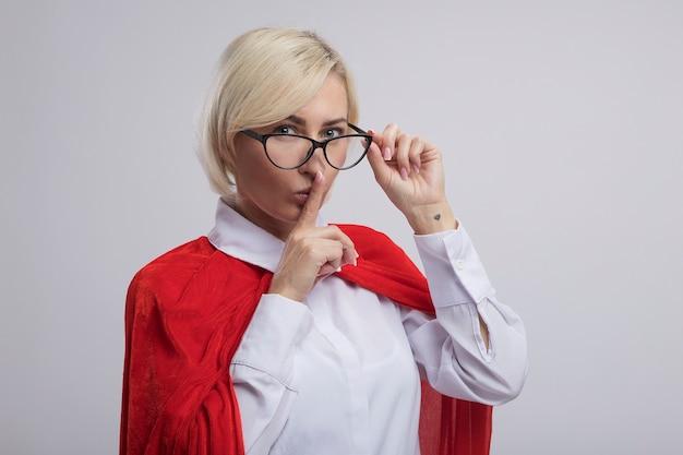 Femme de super-héros blonde d'âge moyen en cape rouge portant et saisissant des lunettes faisant un geste de silence