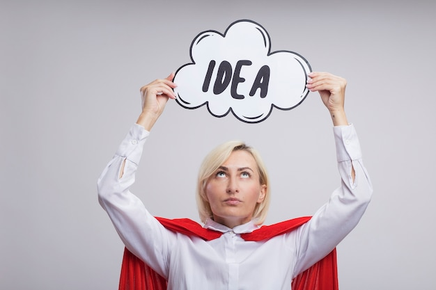 Femme de super-héros blonde d'âge moyen en cape rouge tenant une bulle d'idée au-dessus de la tête en la regardant