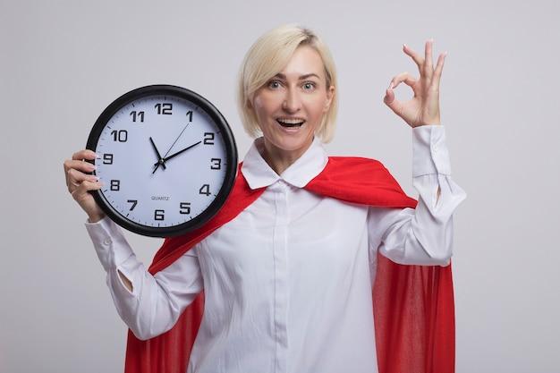 Femme super-héros blonde d'âge moyen en cape rouge tenant une horloge regardant à l'avant faisant signe ok isolé sur mur blanc
