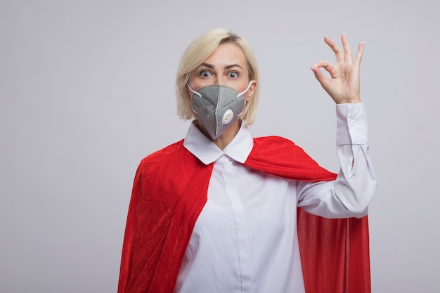 Femme de super-héros blonde d'âge moyen impressionnée en cape rouge portant un masque de protection regardant à l'avant faisant signe ok isolé sur mur blanc avec espace de copie