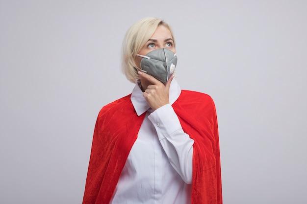 Femme super-héros blonde d'âge moyen réfléchie en cape rouge portant un masque de protection gardant la main sur le menton levant isolé sur mur blanc avec espace de copie